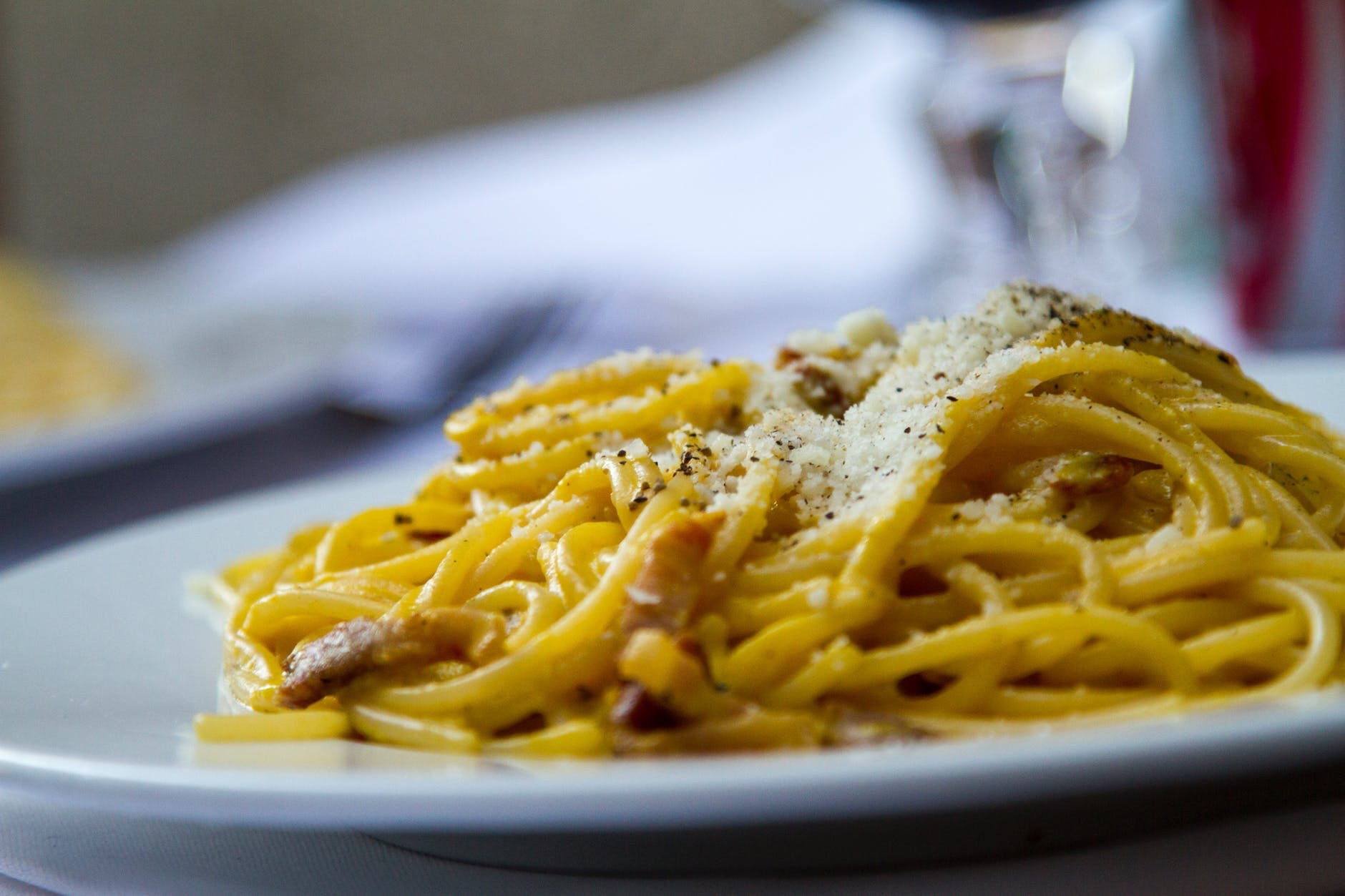 Plate of spaghetti Alfredo with Parmesan sprinkled on top
