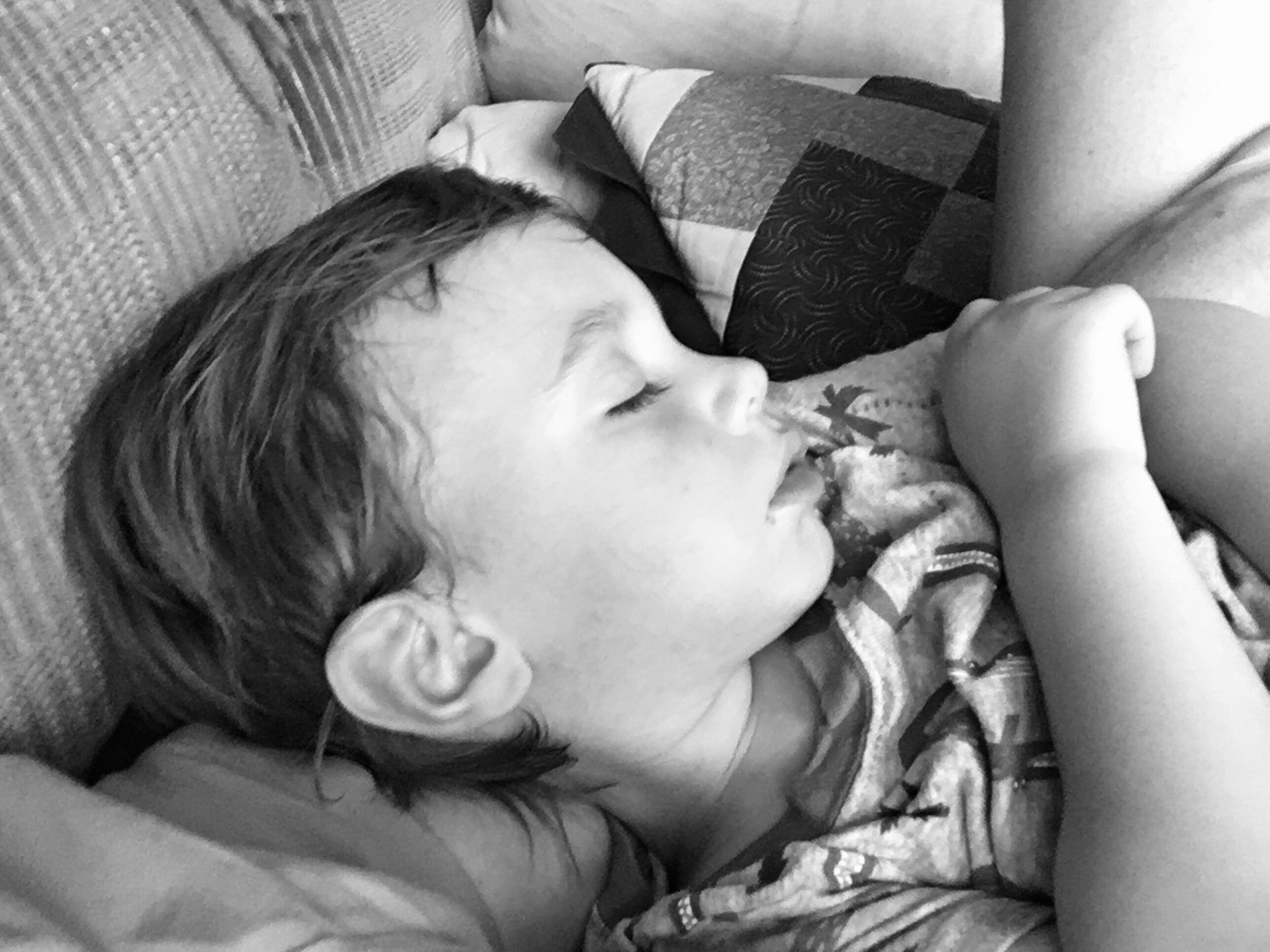 Young boy asleep in mother's arms