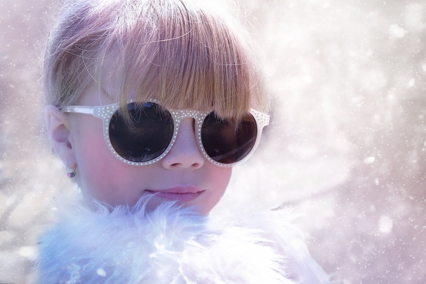 Girl with blonde hair wearing sunglasses and a white feather boa.