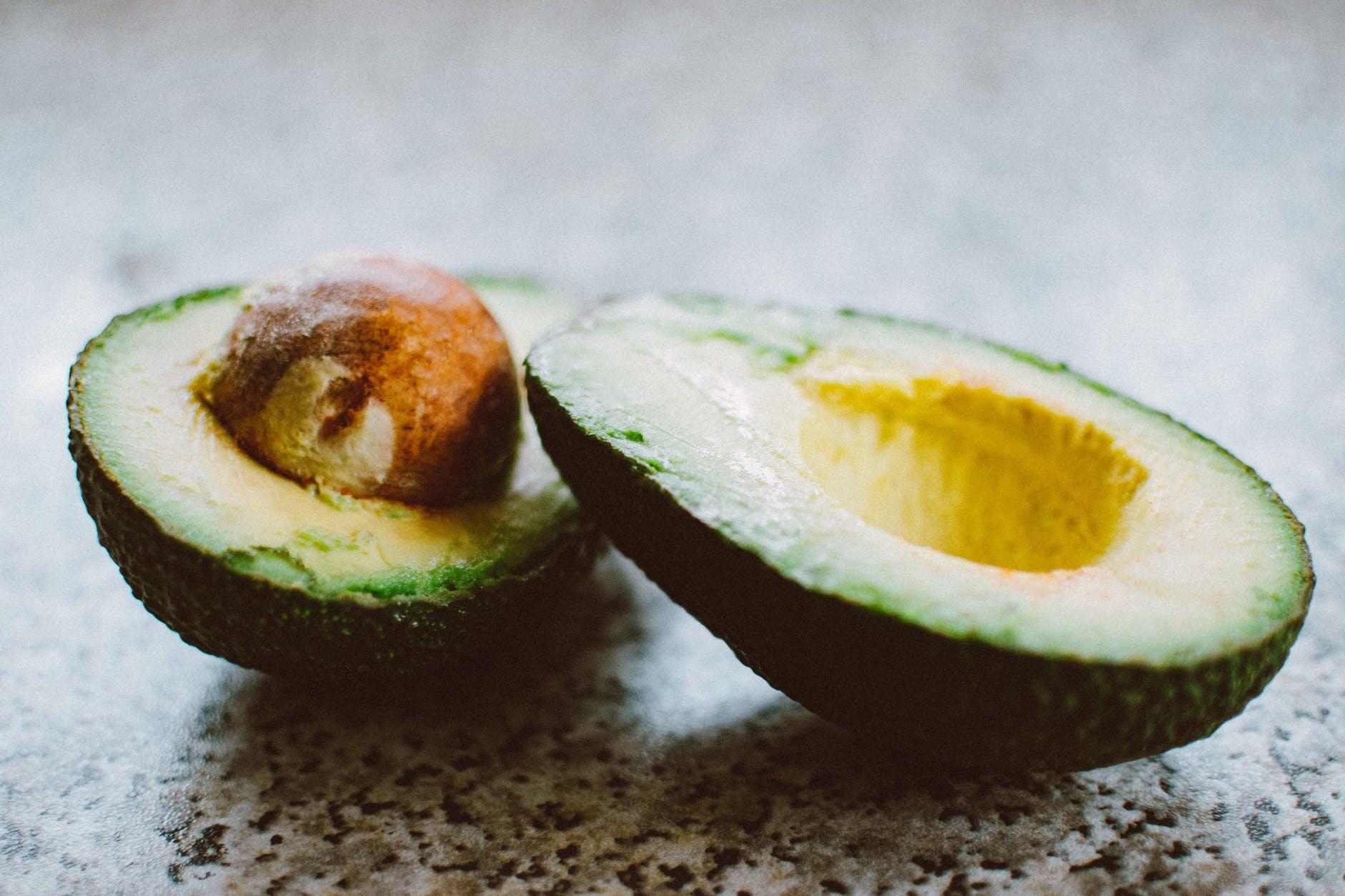 Avocado cut in half on a counter
