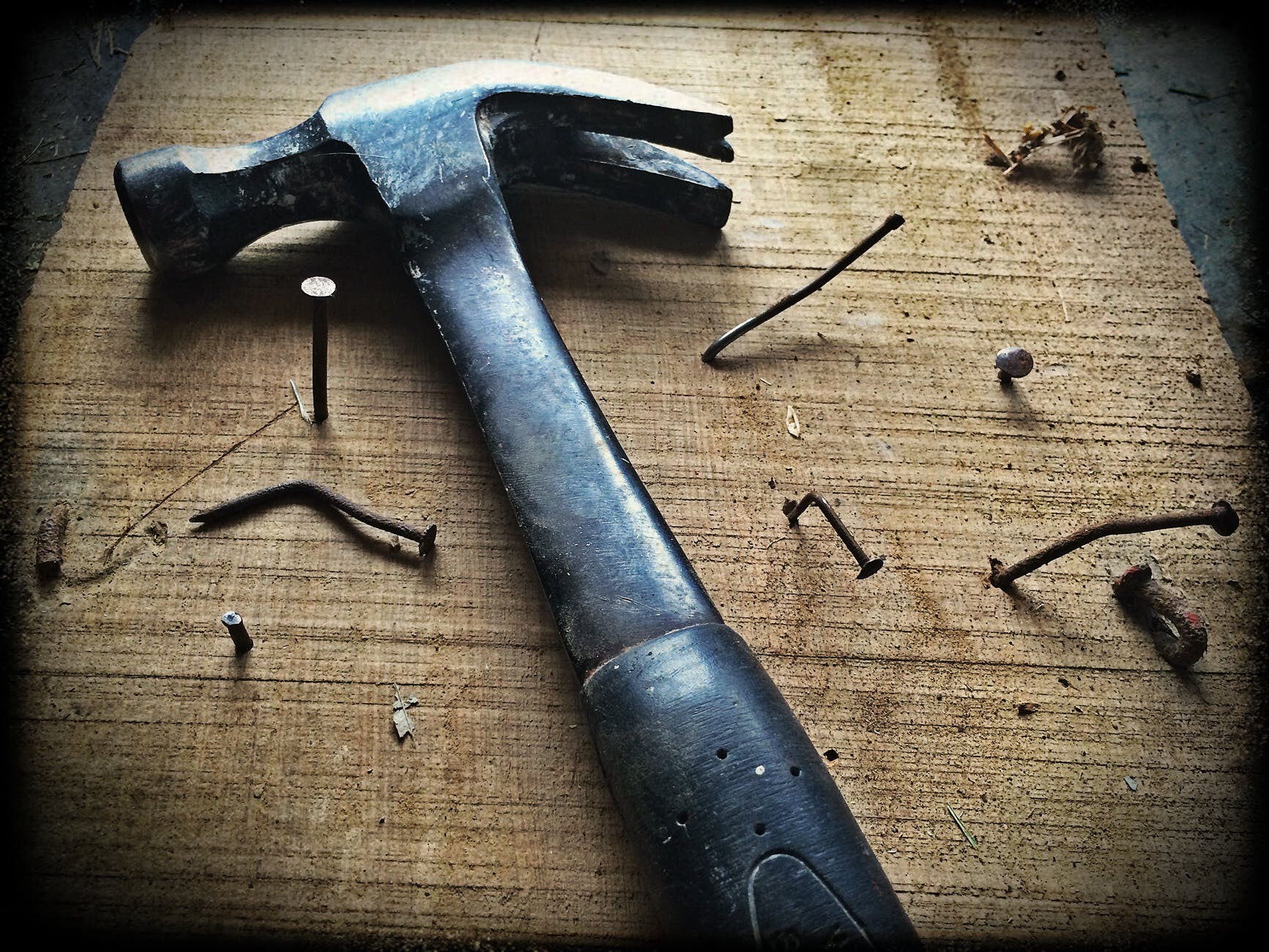 Black and silver hammer laying on a piece of wood with various nails driven into it with varying degrees of success — some are bent, others only part way in