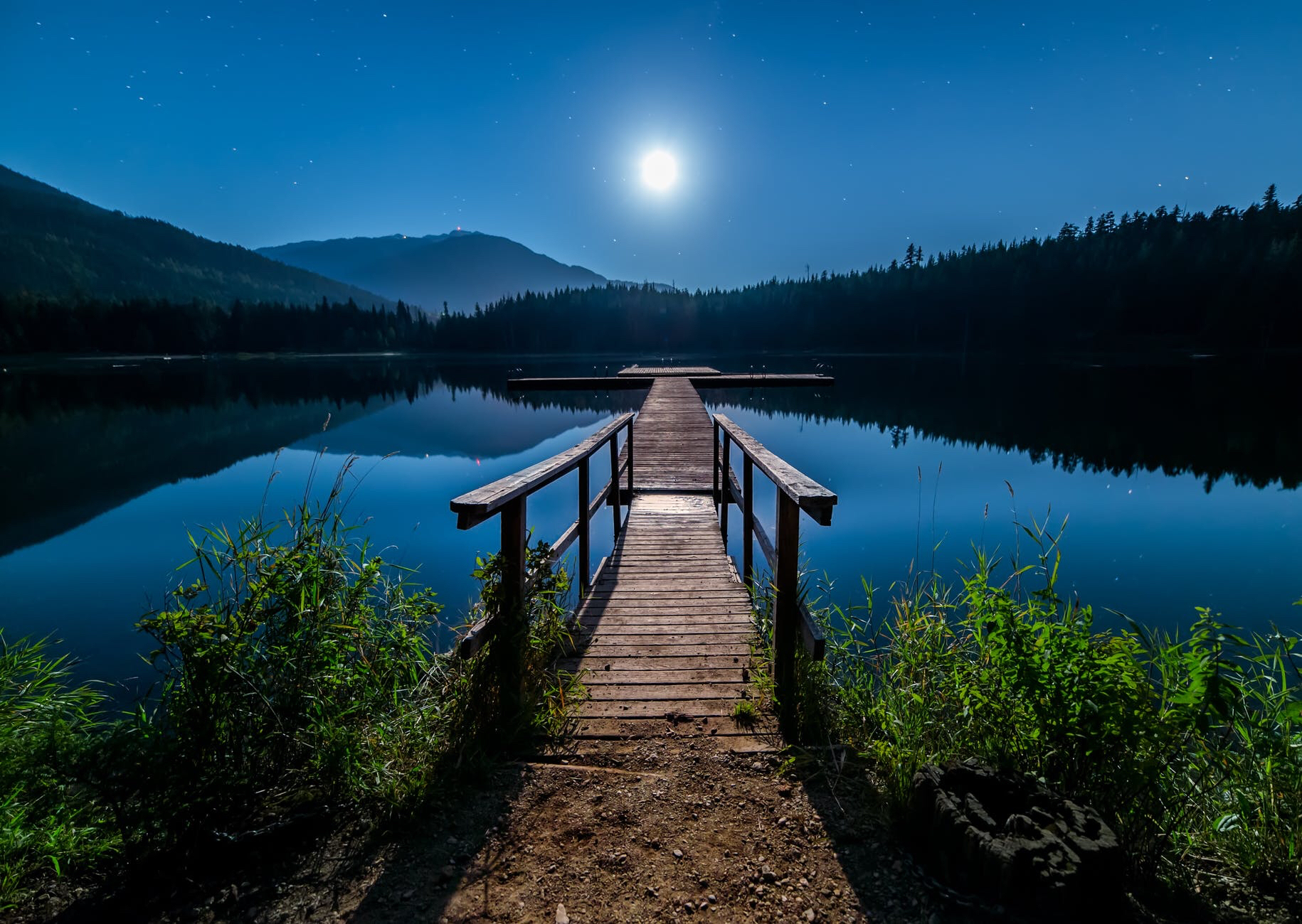 Wooden dock on a lake in the moonlight